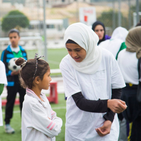 Trainers give instructions on football, girls football, Jordan