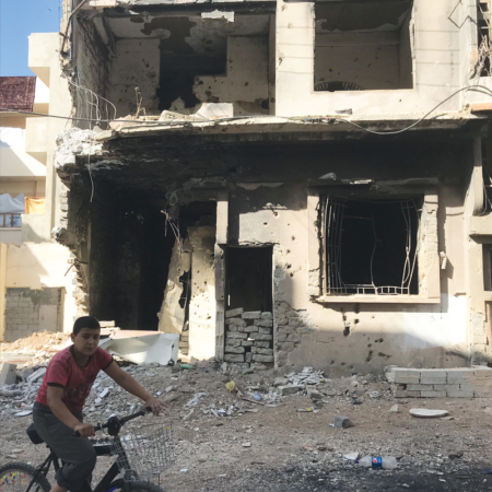 Help in Syria - Boy in front of a bombed house in Homs